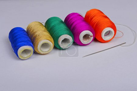 Colorful bobbins of thread with needle