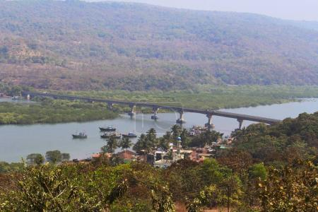 River view with homes, temples and bridge, Anjarle, Kokan