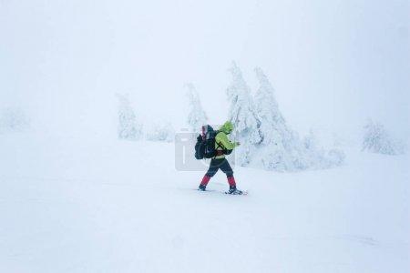 Photo pour Alpiniste aux prises avec un blizzard hivernal dans les montagnes de Gorgany - image libre de droit