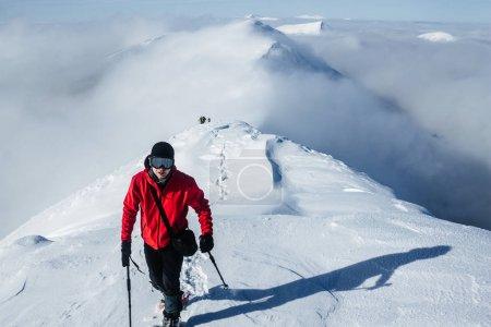Photo pour Leader grimpeur marchant devant l'équipe dans les montagnes enneigées de Gorgany - image libre de droit