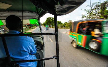 Photo for View from passenger seat when riding tuk tuk (three wheel auto rickshaw) with another one coming in opposite direction on the other side way of road. Malindi, Kenya - Royalty Free Image