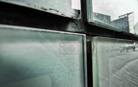 Photo pour Détail abstrait de vitres sales sur le côté du bâtiment reflétant la rue de la ville. Londres, Royaume-Uni - image libre de droit