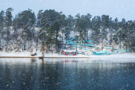Photo pour Toboggan aquatique vide avec cabane de plage rouge près d'un lac gelé par une journée froide d'hiver avec neige dans les nuages. Suède - image libre de droit