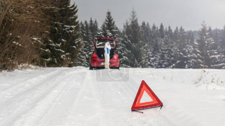 Photo for Bright red triangle on a snowy road warning other drivers with woman standing next to broken car in forest, calling repair service on her mobile phone. - Royalty Free Image