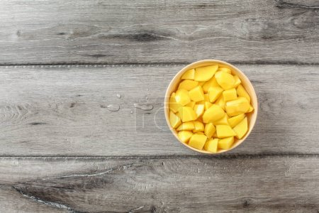 Photo for Table top view on raw potatoes cut in small pieces in beige bowl with water, prepared for cooking, on grey wood desk. - Royalty Free Image