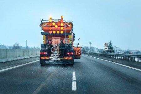 Photo pour Vue de la voiture derrière le camion orange d'entretien de la route répandant du sel de dégivrage et du sable, des cristaux tombant sur la route asphaltée recouverte de glace . - image libre de droit