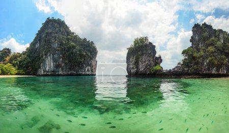 Photo pour Panorama de falaises karstiques pointues s'élevant de l'eau avec une mer verte claire pleine de poissons au premier plan. Hong Islands, Thaïlande - image libre de droit
