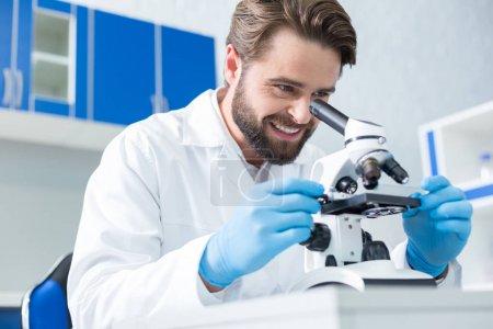Photo pour Expérience réussie. Joyeux scientifique intelligent positif regardant au microscope et souriant tout en étant satisfait de ses résultats de recherche - image libre de droit