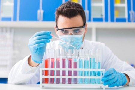 Ein Tropfen. konzentrierte geschickte männliche Laborant mit Pipette zum Einfüllen von Flüssigkeit in Fläschchen, während sie im Stand stehen