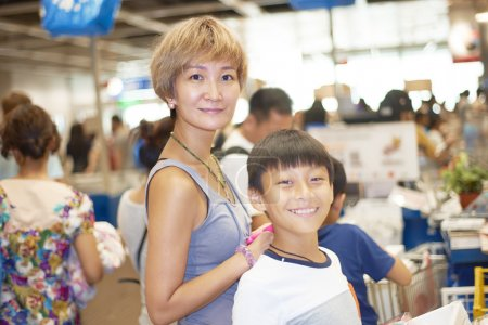mother and son waiting for checkout in shopping mall