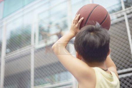 Photo pour Asiatique garçon se préparer pour basket-ball tir à aire de jeux - image libre de droit