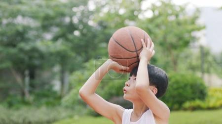 teenage Asian boy playing basketball outdoors preparing for shooting