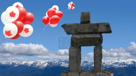 Photo pour Canada Balloons with maple leaf floating over an inukshuk in the Rocky mountains. - image libre de droit