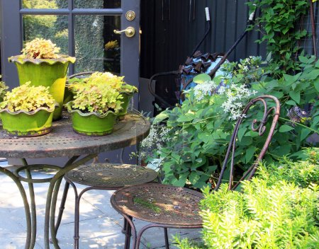 Photo for Springtime garden with patio furniture and potted perennials. - Royalty Free Image