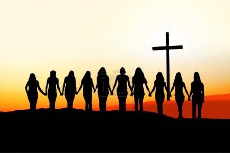 Photo pour Sunset silhouette of 10 young women walking hand in hand toward a Christian Cross. - image libre de droit