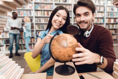 Photo pour Ethnique asiatique fille et blanc gars assis à la table entouré de livres dans la bibliothèque et en utilisant globe - image libre de droit