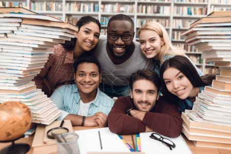 Six ethnic students, mixed race, indian, asian, african american and white sitting at table surrounded with books at library