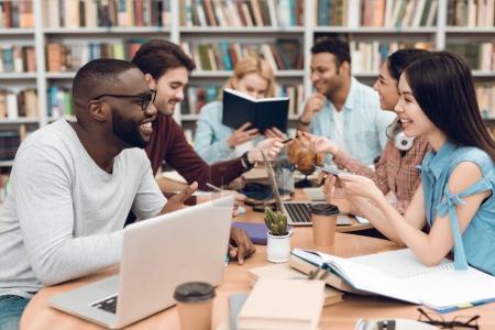 Photo pour Groupe d'étudiants ethniques multiculturels assis et étudiant à table à la bibliothèque - image libre de droit