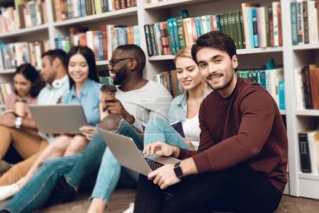 Group of ethnic multicultural students sitting, smiling and talking near bookshelves in library