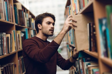 White student in sweater with books in library surrounded by books