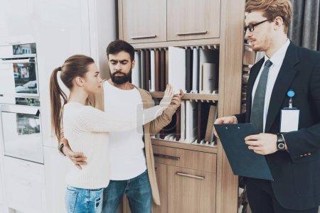 Photo pour Couple de clients avec gestionnaire en costume choisir des matériaux d'armoire dans le magasin de cuisine - image libre de droit