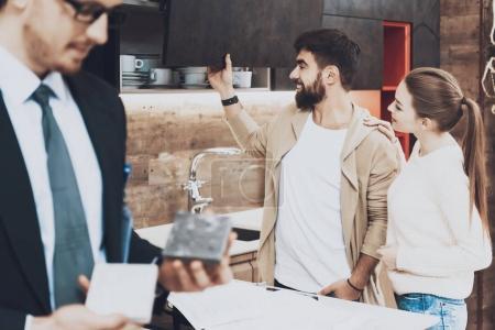 Photo pour Gestionnaire en costume montrant différents matériaux avec des clients de couple sur fond dans le magasin de cuisine - image libre de droit