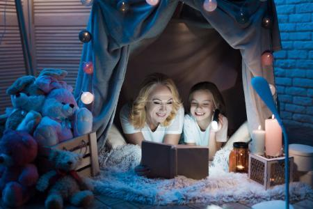 Grandmother and granddaughter reading book in blanket house with flashlight at home
