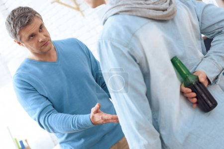 Angry drunk father asking his son giving back his beer
