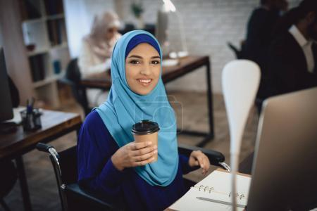 Disabled Arab woman in wheelchair working on desktop computer and drinking coffee