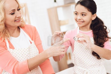 Young grandmother with grandchildren preparing cookies at kitchen