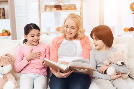 grandmother with granddaughter and grandson looking photo album at home