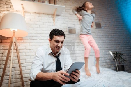 Businessman trying working on tablet while girl preventing father from working