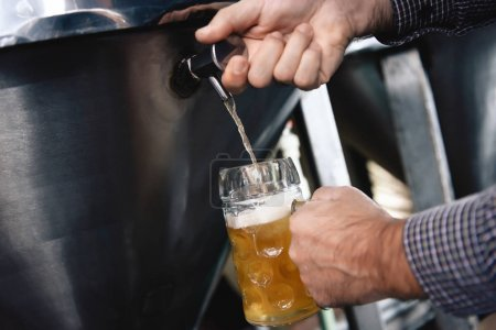 male hands pouring beer in tumbler from beer tap at craft brewery