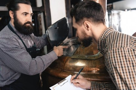 Two bearded brewers inspecting equipment of brewery for production of craft beer