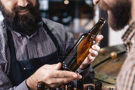 Bearded man holding empty bottle intended for craft beer at brewery