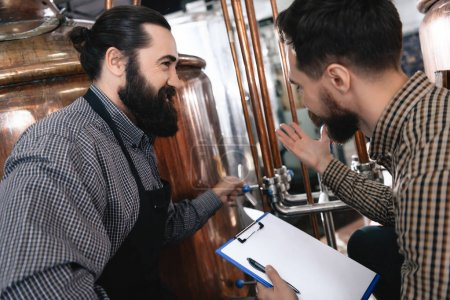 Photo for Two bearded brewers inspecting equipment of brewery for production of craft beer - Royalty Free Image