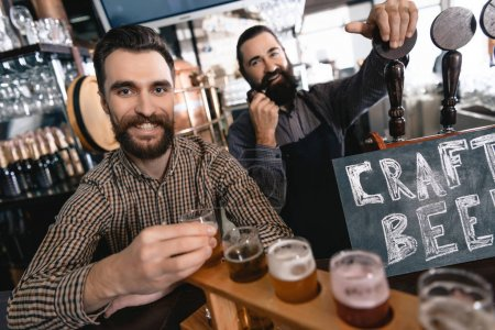 Brewer checking quality of fresh beer at craft brewery