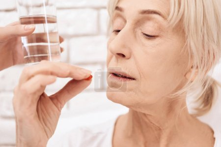 Girl nursing elderly woman in bed at home and bringing water and pills