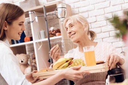 Photo pour Fille de prendre soin d'une femme âgée en fauteuil roulant et apportant le petit déjeuner sur le plateau - image libre de droit