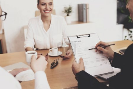 HR director woman in blouse and skirt sitting while boss looking at resume at job interview