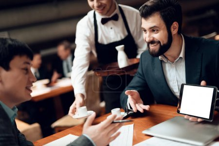 businessmen meeting in restaurant and looking at tablet while waiter bringing coffee