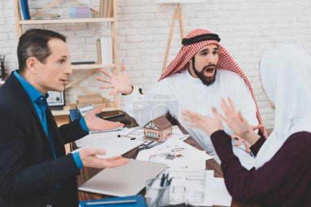 Angry Arab in kufiya screaming on upset woman at office of realtor