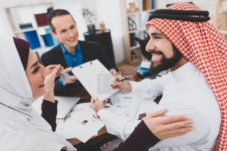 Arab couple signing contract of sale in office of realtor, concept of house buying