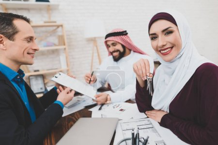 Muslim couple signing purchase and sale agreement in real estate agency