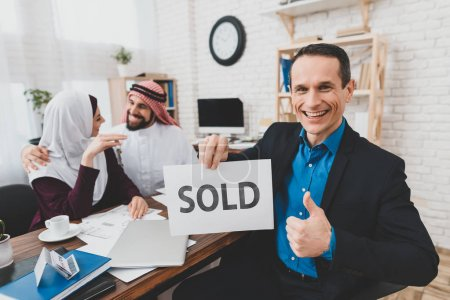 Young Arab couple bought new house, realtor holding sign with inscription Sold