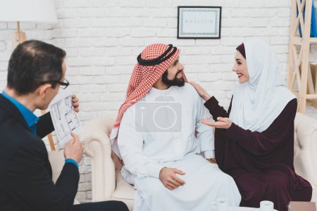 realtor showing house plan for Arab couple in real estate agency