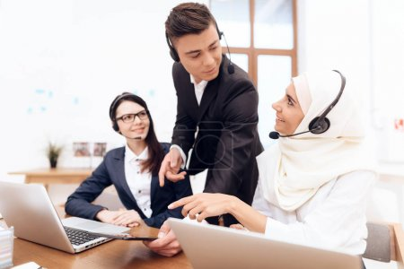Photo for Arab woman and her colleagues working operators in call center - Royalty Free Image