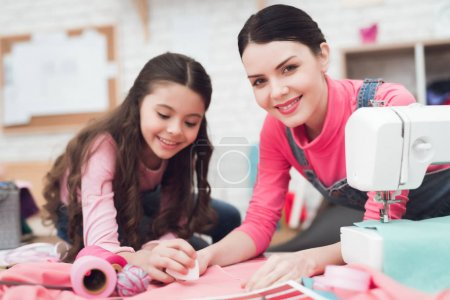 Mom and daughter sew clothes in sewing workshop