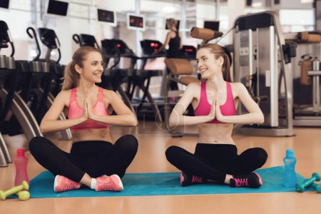 Mother and daughter in sportswear doing yoga poses at gym
