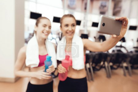 Photo for Mother and daughter in sportswear taking selfie at gym - Royalty Free Image